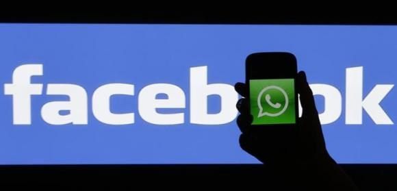 A woman holds a smartphone displaying WhatsApp's logo in front of the screen with the Facebook logo in this photo illustration taken in Prague February 20, 2014