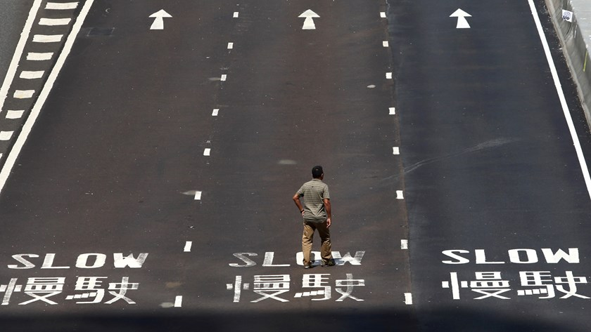 A man walks along Connaught Road Central in Hong Kong, China, on Oct. 6, 2014.