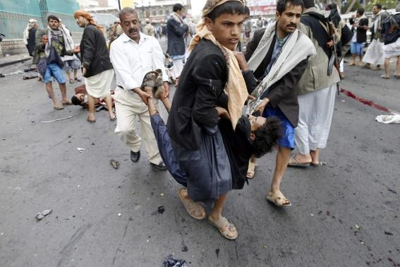 Shi'ite Houthi rebels carry a wounded man at the scene of a suicide attack in Sanaa October 9, 2014.