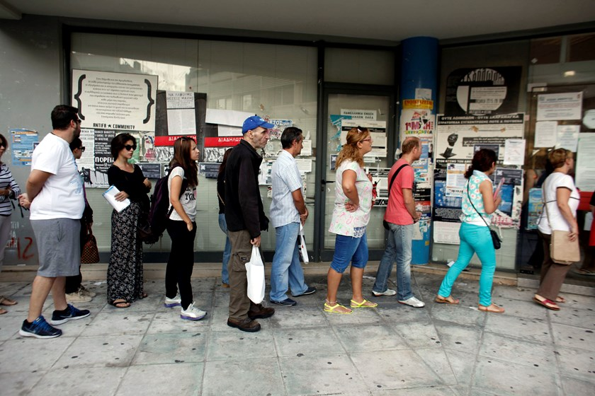 Jobseekers queue to enter an OAED employment center shortly after opening in Athens, Greece, on Wednesday, Sept. 10, 2014.