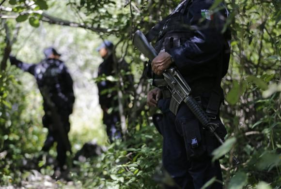Iguala police officers stand guard at an area near clandestine graves at Pueblo Viejo, in the outskirts of Iguala, southern Mexican state of Guerrero October 9, 2014.