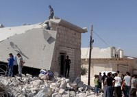 Syrians inspect the rubble of destroyed houses following the U.S.-led coalition's airstrikes against the Islamic State of Iraq and the Levant on a residential area in Idlib, Syria, on Sept. 23, 2014.