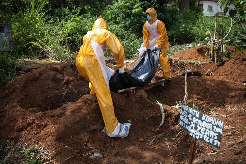 A team of funeral agents specialised in the burial of Ebola victims put a body in a grave at the Fing Tom cemetery in Freetown, on October 10, 2014