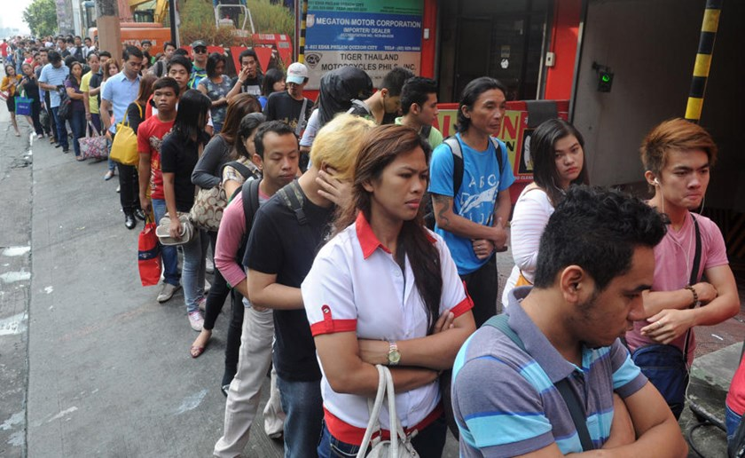 Commuters queue to ride the light rail transit in Quezon City in suburban Manila on October 10, 2014