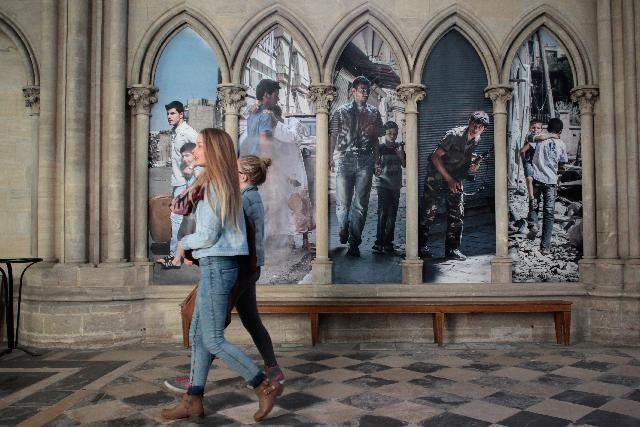 People walk in the Cathedral of Bayeux during an exhibition dedicated to the work of French photojournalist Laurent Van Der Stockt in Syria, on October 11, 2014 in Bayeux
