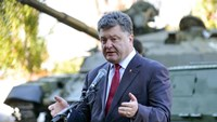 Ukraine's President Petro Poroshenko delivers a speech in front of a new tank at the Malyshev factory in Kharkiv on October 11, 2014