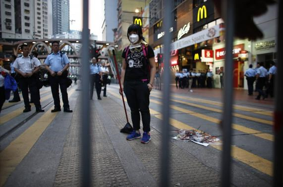 A pro-democracy protester takes a break as she sweeps a street after policemen removed some barricades, at a protest site at the commercial area of Causeway Bay in Hong Kong October 14, 2014.