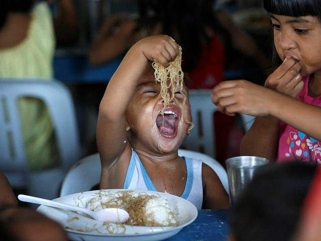A boy enjoys free meals during a feeding program at a slum community in Manila October 28, 2011.