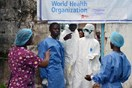 Health workers in protective gear pose at the entrance of the Ebola treatment unit of the John F. Kennedy Medical Center, in the Liberian capital Monrovia, Liberia, on Oct. 13, 2014.