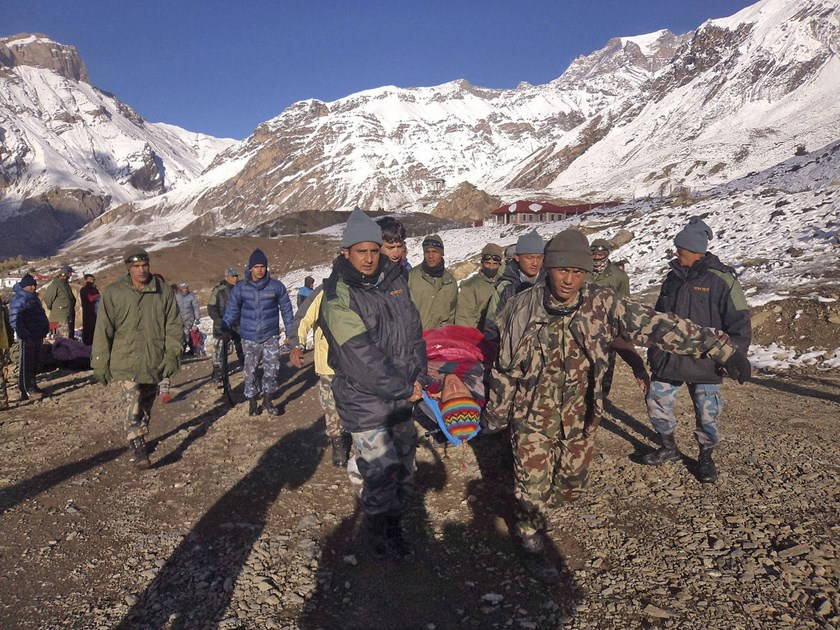 In this photo provided by the Nepalese army, soldiers carry an avalanche victim before he is airlifted in Thorong La pass area, Nepal, on Oct. 15, 2014.