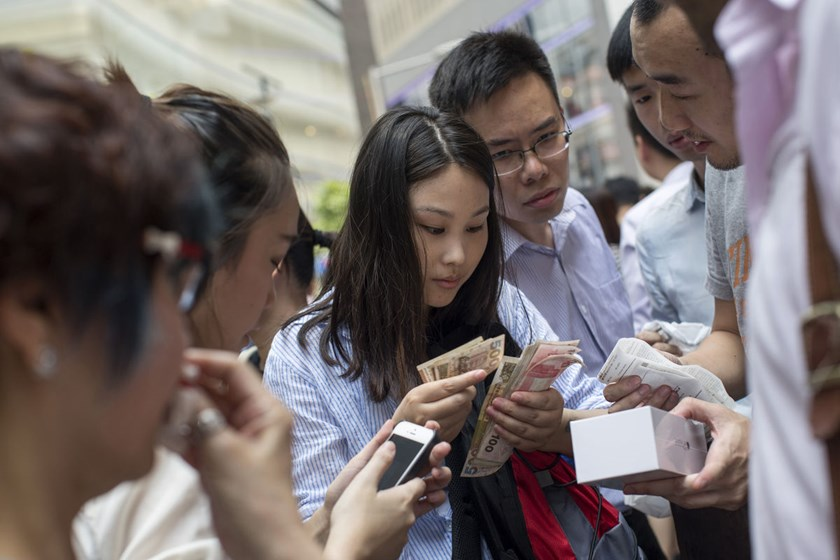 A woman counts Hong Kong dollar banknotes as people resell Apple Inc. iPhones across from the company's Causeway Bay store during the sales launch of the iPhone 6 and iPhone 6 Plus in Hong Kong, China.