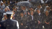 Russian President Vladimir Putin, third from right, is seen through a heavy rainfall during a military parade in Belgrade on Oct. 16, 2014.