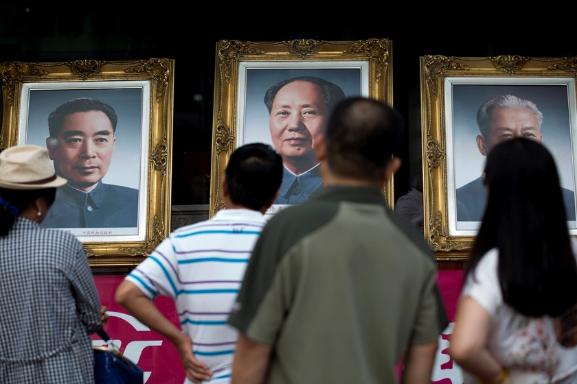 People look at portraits of former Chinese leaders Zhou Enlai, left, Mao Zedong, center, and Liu Shaoqi displayed in a shop on Wangfujing Street in Beijing, China.