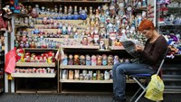 A vendor sits and reads a newspaper beside a souvenir stand selling matryoshka dolls in St. Petersburg.
