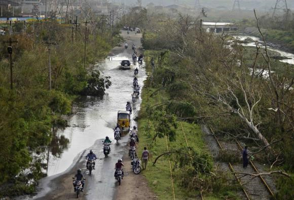 Vehicles move through a flooded road next to the trees fallen over railway tracks after being damaged by strong winds caused by the Cyclone Hudhud in the southern Indian city of Visakhapatnam October 14, 2014.