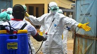 Guinea's Red Cross health workers get their protective suits prepped to carry the body of an Ebola victim at a treatment center in Conakry, on Sept. 14, 2014.