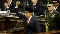 "Indonesian President Joko Widodo, center, shouts ""freedom"" while raising his fist as he delivers his speech during his inauguration ceremony as the country's seventh president at the parliament building in Jakarta, Indonesia. Close"