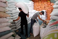 Workers load bags of rice to a store outside Hanoi.
