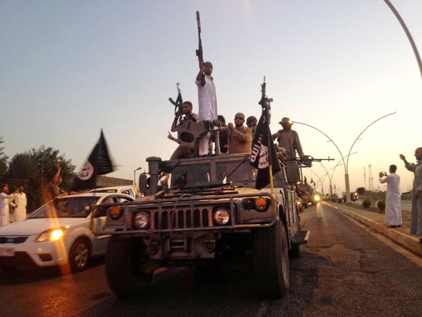 In this Monday, June 23, 2014 file photo, militants from the Islamic State parade down a main street Mosul, Iraq, in a commandeered Iraqi security forces armored vehicle.