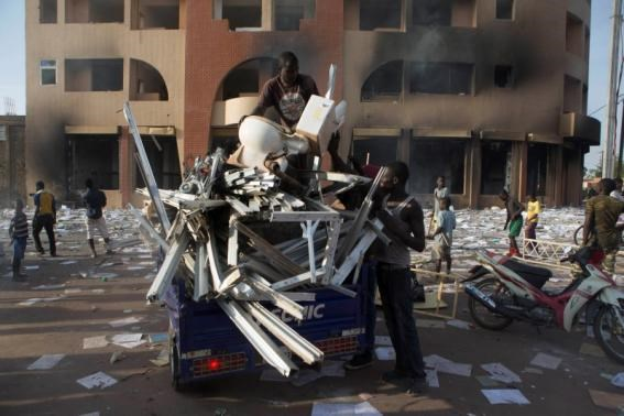 People load goods looted from a building, which according to locals, belongs to Francois Compaore, the younger brother of Burkina Faso's President Blaise Compaore, in Ouagadougou, capital of Burkina Faso, October 30, 2014.