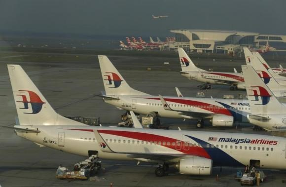Ground crew work among Malaysia Airlines planes on the runway at Kuala Lumpur International Airport (KLIA) in Sepang July 25, 2014.