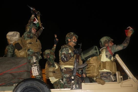 Kurdish Peshmerga fighters celebrate atop an army vehicle carrying a heavy machinegun as they move towards the Syrian town of Kobani, October 31, 2014.