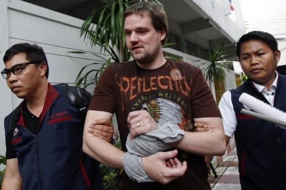 Hans Fredrik Lennart Neij (C), a co-founder of the Swedish file-sharing website, The Pirate Bay, is escorted by Thai police officers as he arrives at the Immigration Detention Center in Bangkok November 5, 2014.