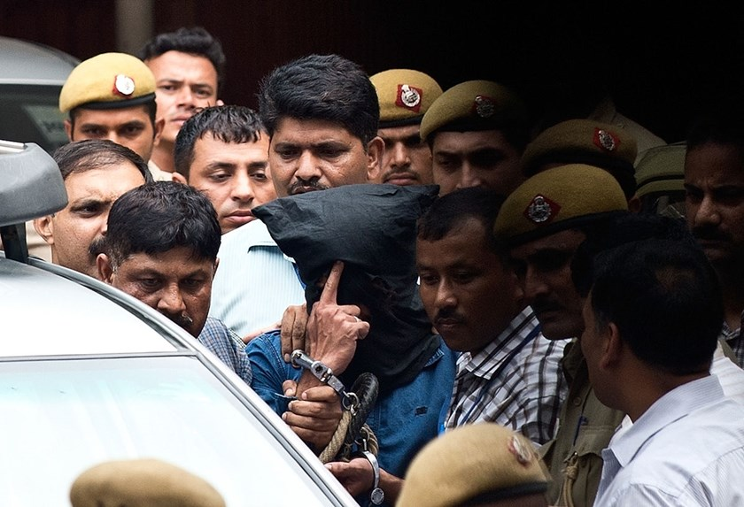 India's National Investigating Agency (NIA) personnel escort a hooded suspect (C) believed to be Yasin Bhatkal, the alleged founder of militant group Indian Mujahideen, at the Patiala House courts in New Delhi on August 30, 2013.