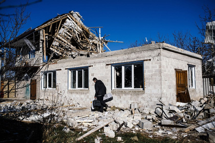 A man carries his belongings as passes by his destroyed home following shelling in the Kuybeshevski area in Donetsk on Nov. 6.