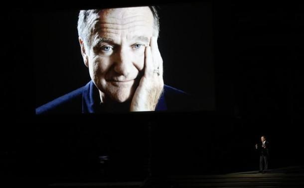 Billy Crystal takes the stage to pay tribute to the late Robin Williams, shown on a large screen, during the 66th Primetime Emmy Awards in Los Angeles, California August 25, 2014.