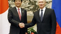 Russia's President Vladimir Putin (R) and Japan's Prime Minister Shinzo Abe shake hands before their talks in Beijing November 9, 2014, in this photo taken by Kyodo.