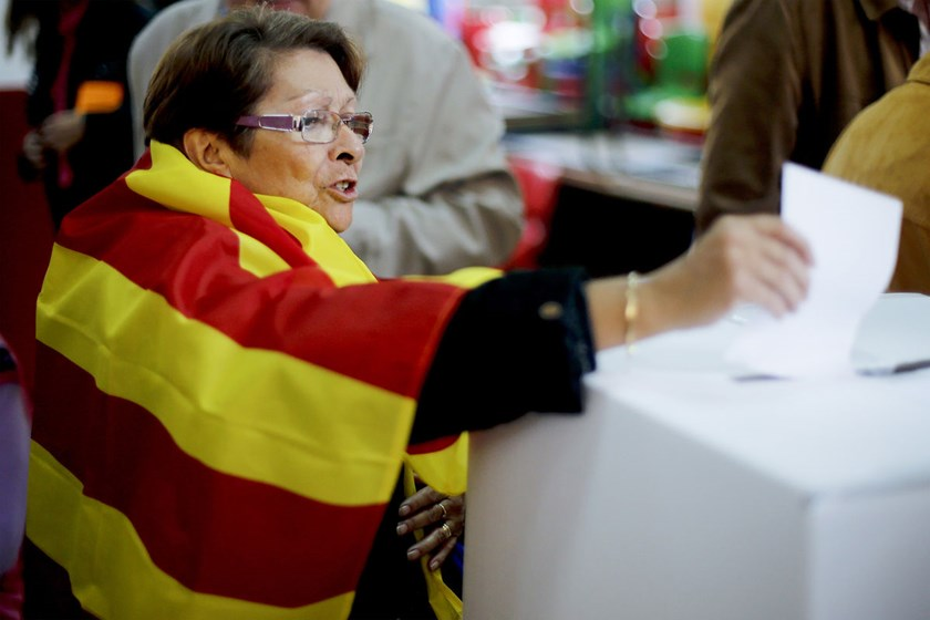 A woman draped in a Catalan pro-independence flag casts her vote into the ballot box at a polling station in Barcelona, Spain today.
