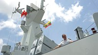 A crew member of the Chinese Navy looks out from the deck of Chinese navy ship Wei Fang as it approaches the dock at the Myanmar International Terminal Thilawa port on the outskirts of Yangon on May 23, 2014.