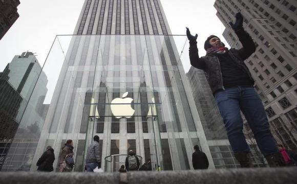 A man poses for a photo in front of the Apple store on 5th Avenue in New York, December 26, 2013.