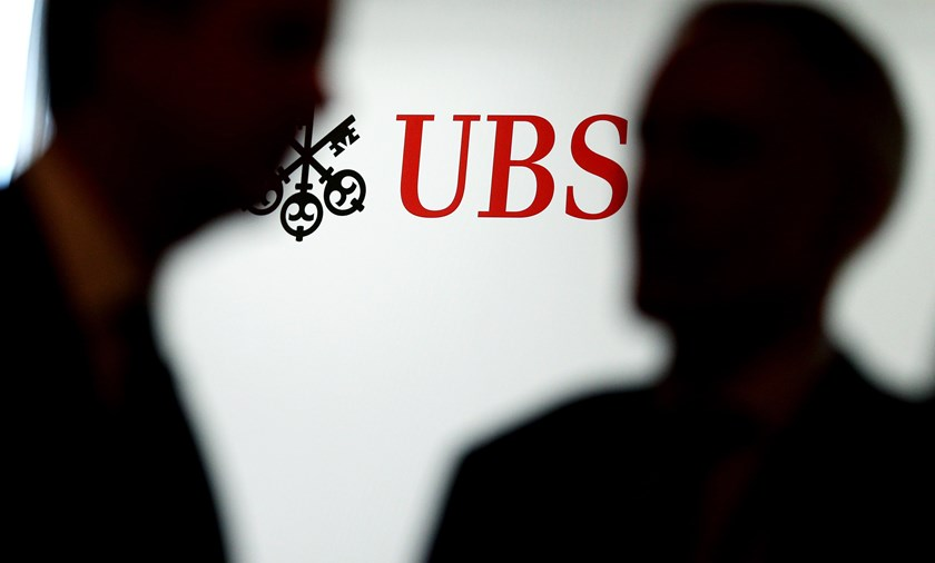 Attendees pass an advertisement for UBS AG during a break in sessions at the Swiss International Finance Forum (SIFF) in Bern on May 20, 2014.