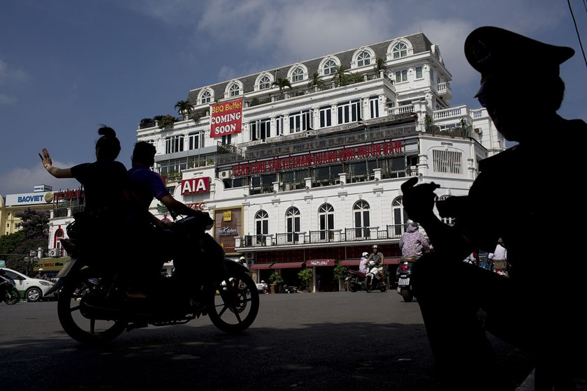 Commuters on a motorcycle ride past a commercial building in Hanoi, Vietnam. The Southeast Asian nation is stepping up efforts to resolve bad debt that has crimped lending to businesses and pushed economic growth below 6 percent for two straight years.