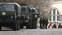 Armed people and military trucks are seen near a checkpoint outside a building on the territory controlled by the self-proclaimed Donetsk People's Republic in Donetsk, eastern Ukraine, November 12, 2014.