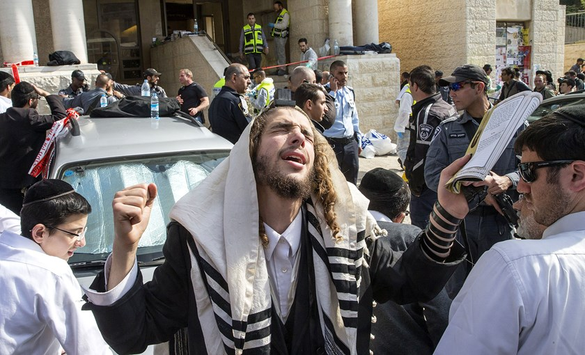 An Ultra-orthodox Jewish man prays at the scene of an attack on Israeli worshippers at a synagogue in the ultra-Orthodox Har Nof neighbourhood in Jerusalem on Nov. 18, 2014.