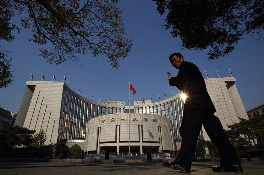 A pedestrian walks past the People's Bank Of China headquarters in the financial district of Beijing.