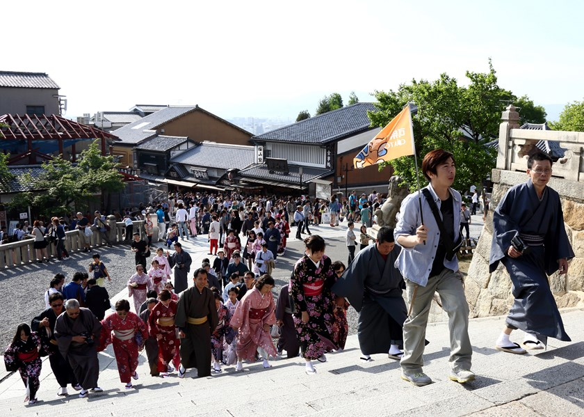 A tour guide holds a flag while leading a group of Chinese tourists wearing rental kimonos at the Kiyomizu-dera temple in Kyoto, Japan.