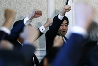 Japan's Prime Minister Shinzo Abe raises his fist with his party's lawmakers at the party lawmakers' meeting after the dissolution of the lower house was announced at the Parliament in Tokyo November 21, 2014.