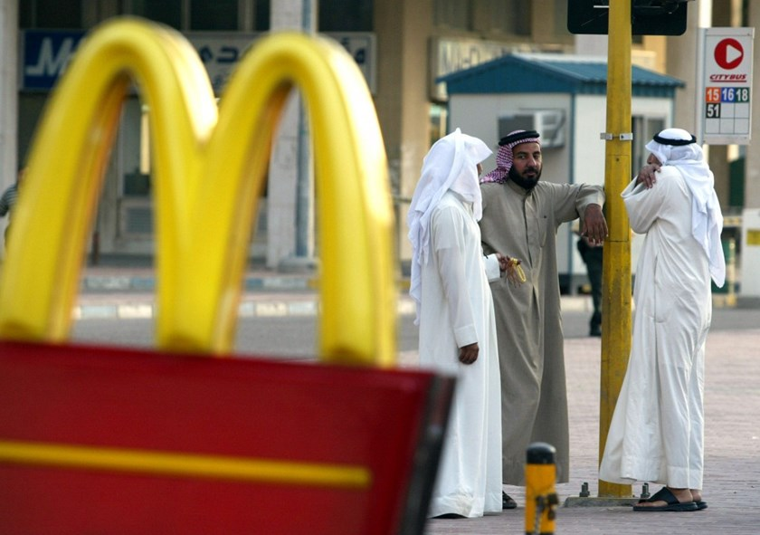 Three Arab taxi drivers chat near a McDonald's restaurant in Kuwait City November 10, 2002.