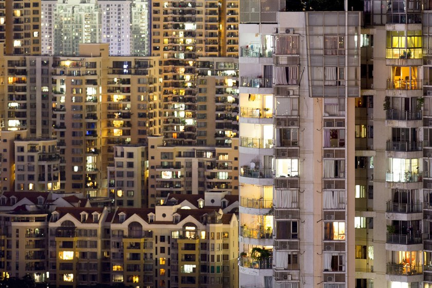 Residential buildings stand illuminated at night in the Nanshan district of Shenzhen, China.