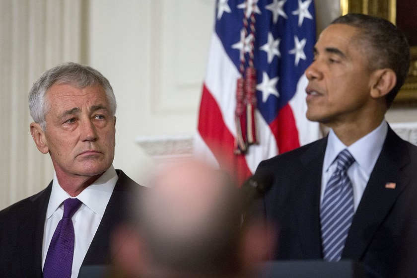 Chuck Hagel, U.S. Secretary of Defense, left, listens as U.S. President Barack Obama speaks in the State Dining Room of the White House in Washington, D.C., U.S., on Nov. 24, 2014.