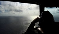 An aircraft captain of the Royal New Zealand Airforce P-3K2-Orion aircraft, helps to look for objects during the search for missing Malaysia Airlines flight MH370 in flight over the Indian Ocean off the coast of Perth, Australia, on April 13, 2014.