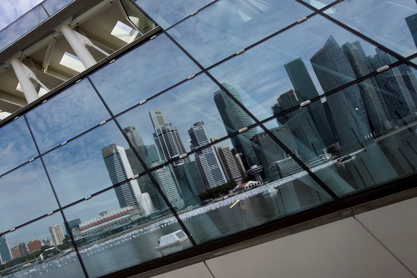 Commercial buildings in the central business district are reflected on a building facade in Singapore, on Monday, Dec. 9, 2013. Singapore's economy may expand 3.9 percent in 2014, according to a median of 21 economists and analysts in the Monetary Authori