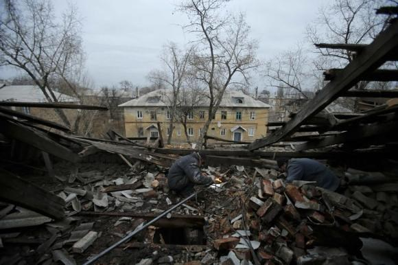 Workers repair a gas pipeline in a building after it was damaged by recent shelling in the western part of Donetsk, eastern Ukraine, November 27, 2014.