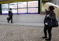A pedestrian looks at an electronic board showing Japan's Nikkei average (top 2nd from L) and various stock prices outside a brokerage in Tokyo November 11, 2014.