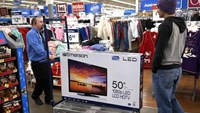 A Walmart employee helps a customer with a 50' TV on sale for $218 on Black Friday in Broomfield, Colorado November 28, 2014.