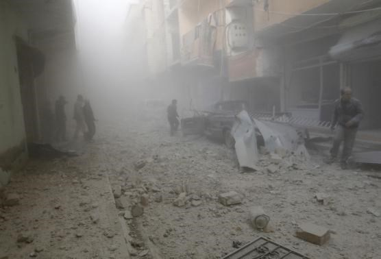 People walk on rubble as they inspect a site hit by what activists said were airstrikes by forces loyal to Syria's President Bashar al-Assad in Raqqa, eastern Syria, which is controlled by the Islamic State November 27, 2014.
